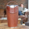 Leather tumbler sleeve for 20 ounce Yeti Rambler cup front sitting on table with carrying strap raised.