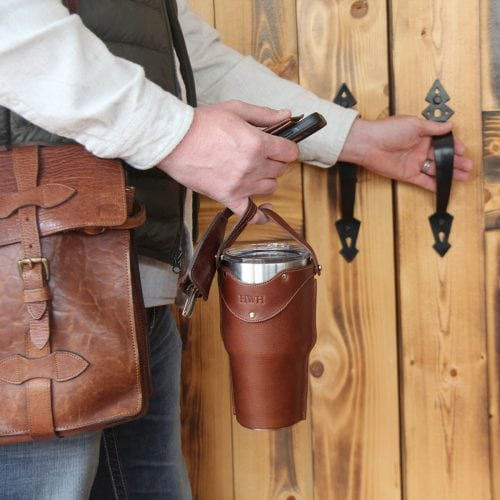 Brown leather tumbler sleeve with Yeti cup being carried out the door by man.