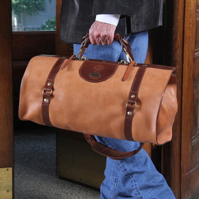Tan Leather duffel bag being carried out a wooden hotel door.