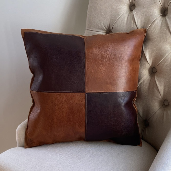 two tone brown leather pillow on cream chair