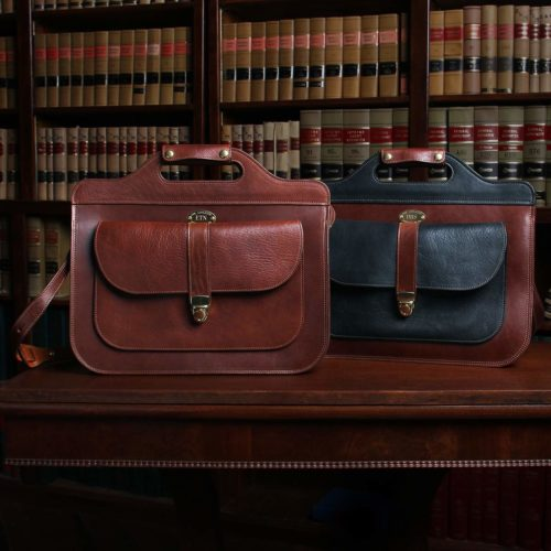 two leather No. 50 Woman briefcases sitting on table